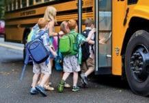 """Kids getting on a school bus"""