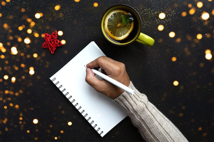 Hand witting a letter to Santa on a black background