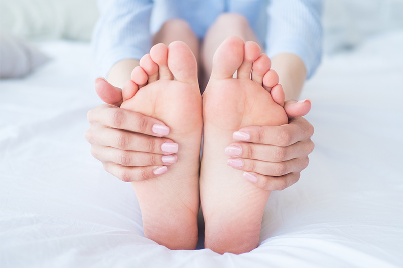 Woman on her bed in pajamas holding her dry feet
