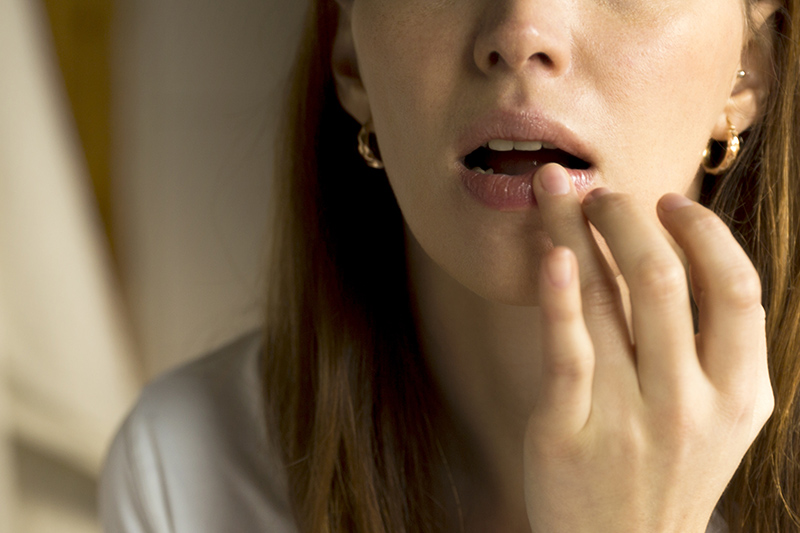Closeup of woman applying ointment to her dry lips with her finger