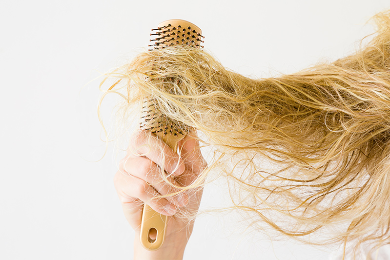 Woman holding a brush connected to her knotty hair