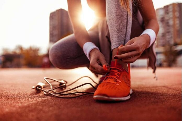 woman keeping up fitness resolution by tying her running shoes