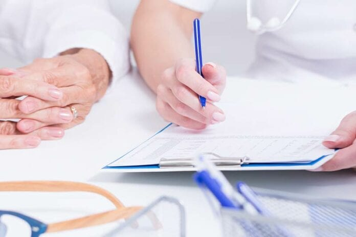 Closeup of nurses interviewing someone with clipboard