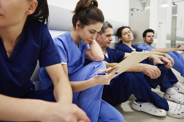 Woman nurse in a line of nurses sitting on the floor tired in blue scrubs