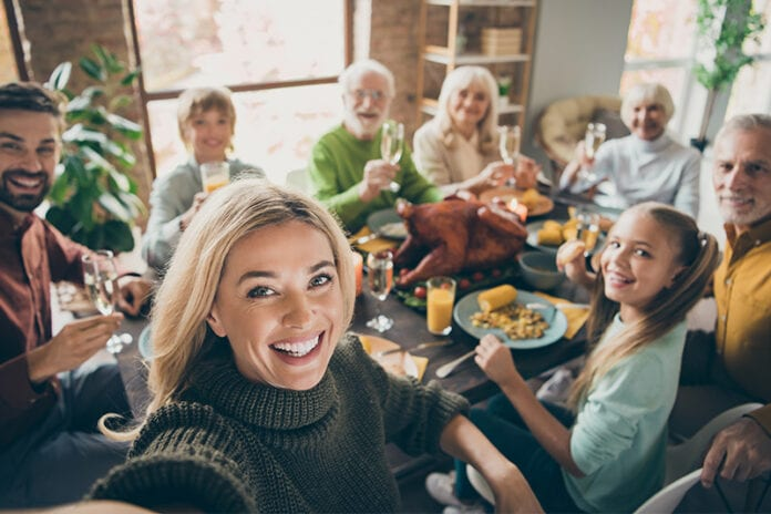 Woman taking selfie with family around thanksgiving dinner