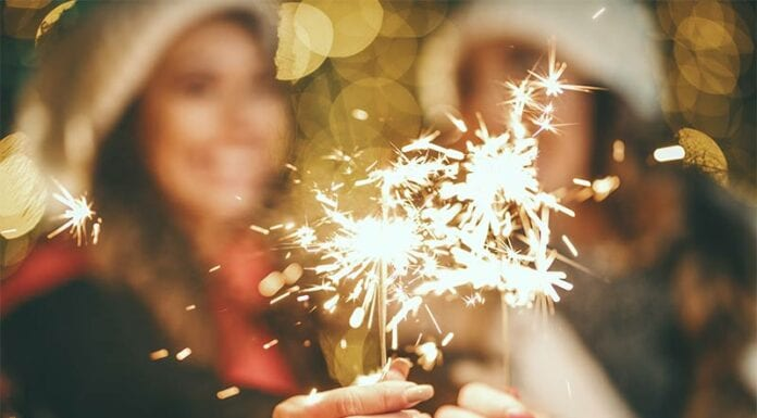 Two women holding up sparklers for news years