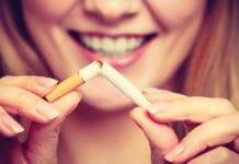 """Smiling woman breaking cigarette"""