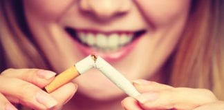 """Smiling woman breaking cigarette"""