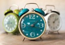 """3 Colorful alarm clocks on table"""