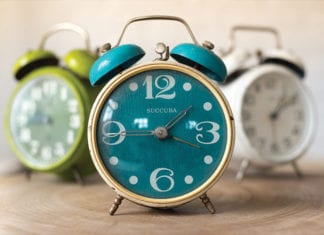 """3 Colorful alarm clocks on table"""