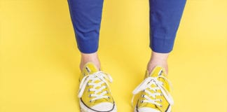 """Feet with yellow converse and purple pants on a yellow background"""