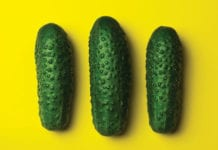"""Three cucumbers in a line on yellow background"""