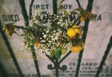 """Yellow flowers on grave fence"""