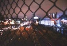 """Busy street through jain link fence"""
