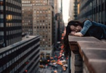 """Sleeping asian woman on city balcony"""