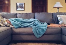 """Woman sleeping under blue blanket on couch"""