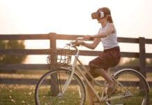 """Young girl riding bike with VR glasses"""
