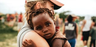 """""""Volunteer woman holding African child"""""""