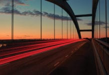 """Lights streaming over bridge at dawn"""