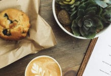"""Muffin, coffee and plant on a wooden table"""