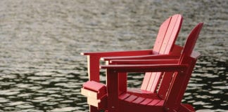 """Two red chairs by the lake"""