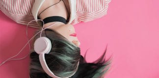 """Girl with white headphones on pink background"""