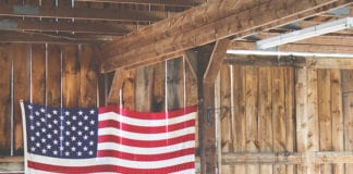 """""""American flag hanging in wooden tack room"""""""