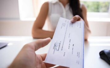 woman handing employee a substantial paycheck
