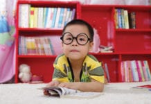 """Small Asian boy wearing glasses reading"""