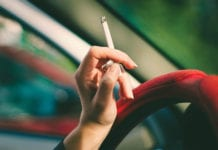 """Woman's hand holding cigarette in car"""