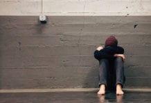 """Sad woman in hallway with head down"""