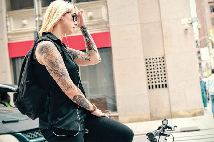 Woman on bike with lots of tattoos