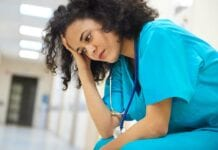Depressed female African American nurse in blue scrubs sitting