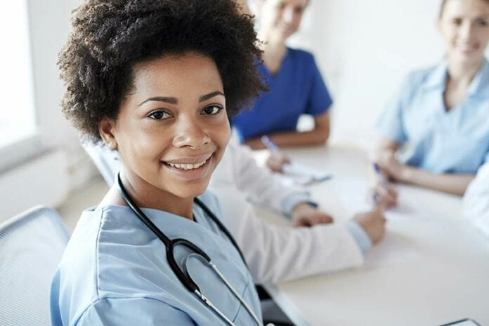 African American female nurse in blue scrubs smiling towards the viewer