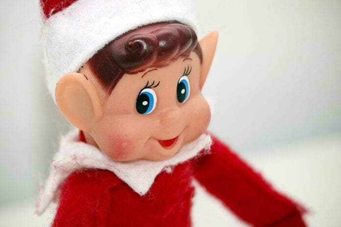 Close-up of elf on the shelf sitting against white background