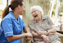Female nurse in blue scrubs laughing with a patient about whet they said