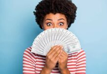 African American woman holding money wondering how to spend it