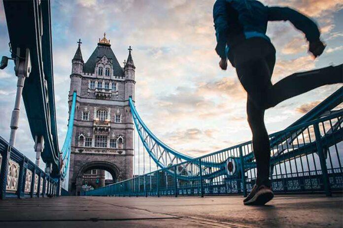 Woman running London Marathon in medical attire