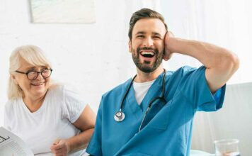 Male nurse in blue scrubs laughing because how hard it can be as a nurse