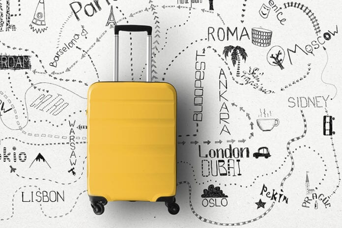 Yellow suitcase laying on hand drawn map of travel destinations